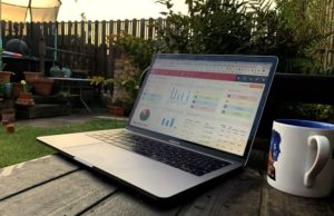 remote working with cloud mrp crm software on laptop and coffee mug on garden bench